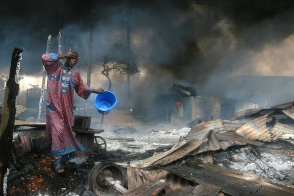 A man rinses soot from his face at the scene of a gas pipeline explosion near Nigeria's commercial capital Lagos December 26, 2006. Up to 500 people were burned alive on Tuesday when fuel from a vandalised pipeline exploded in Nigeria's largest city