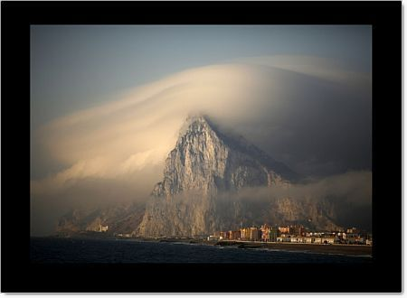 A cloud partially covers the tip of the Rock of the British territory of Gibraltar at sunrise from La Atunara port before Spanish fishermen sail in their fishing boats with their relatives to take part in a protest at an area of the sea where