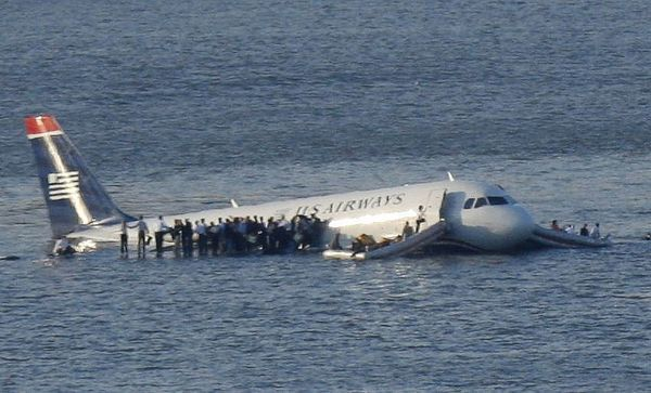 Passengers stand on the wings of a U.S. Airways plane as a ferry pulls up to it after it landed in the Hudson River in New York, January 15, 2009. Local media said the plane was an Airbus with 146 passengers and five crew which had just taken off from La Guardia Airport