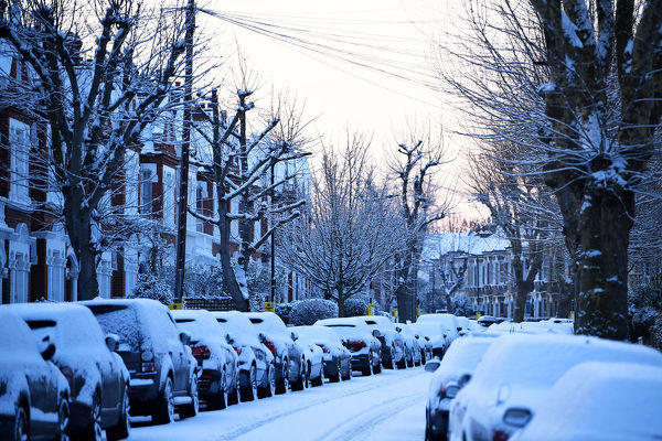 Cars are seen on a snow covered street in South London