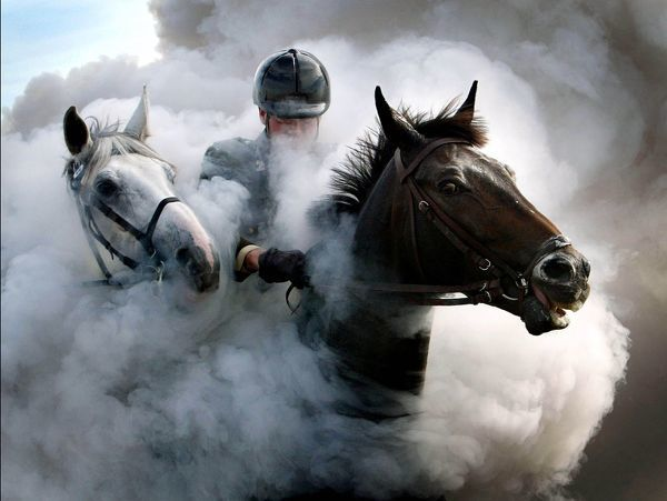 Members of the Dutch Royal Guard ride their horses through clouds of thick smoke and gunfire on the beach of Scheveningen, near The Hague to prepare for the presentation of the Dutch 2004 Budget Memorandum in The Hague, September 15, 2003
