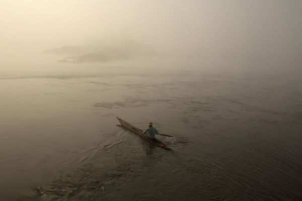 A fisherman paddles his boat on the river Oubangui in Bangui