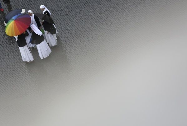 GM1E93D1HFF01. Nuns hold umbrellas in Saint Peter's Square while waiting for smoke to rise