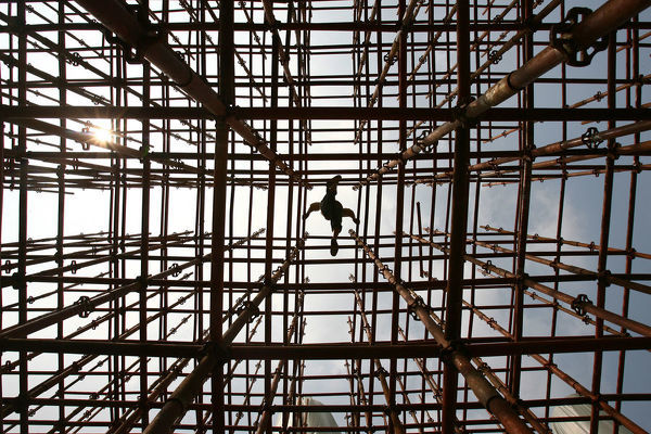 A labourer walks across scaffolding at a construction site in Wuhan, Hubei province August 28, 2006. The Yangtze River metropolis of Wuhan is being transformed as property developers from across China bet that red-hot growth will radiate inland