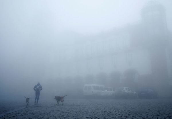A man walks on a street on a foggy day in Sighnaghi