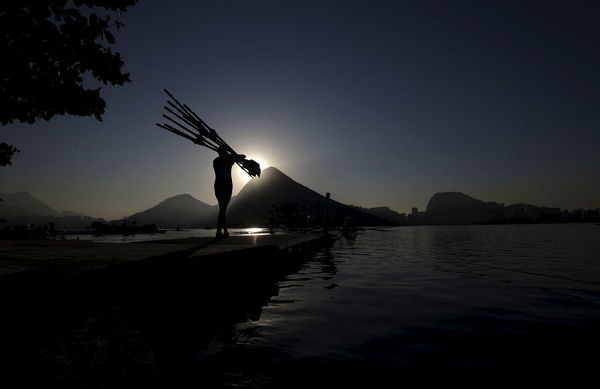 A rowing athlete carries paddles ahead of training session at the World Rowing Junior