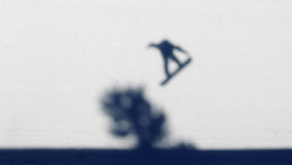 The shadow of a snowboarder is cast over a tree on the half pipe as he takes part in a half pipe practice session at the FIS Snowboard World Championships in La Molina January 17, 2011. The championships take place in Barcelona and La Molina from January 15 to 22