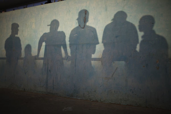 Shadows are cast on the wall of a stadium as people watch a traditional wrestling
