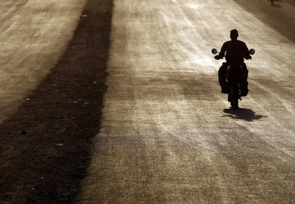 A southern Sudanese man rides a motorcycle during sunset in Juba