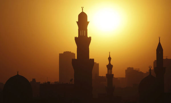The sun sets over the minarets of mosques during the holy fasting month of Ramadan