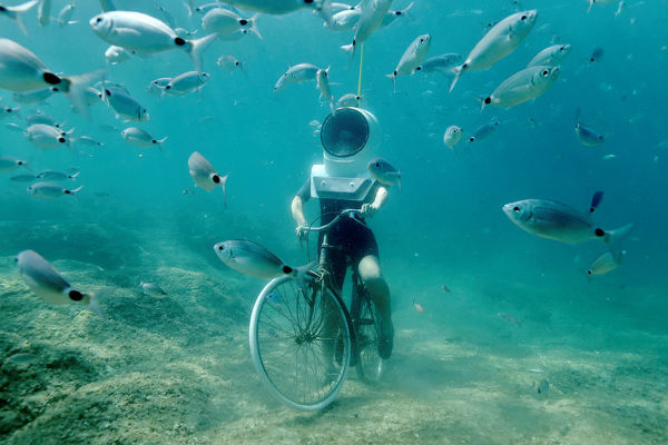 A woman dives and pretends to ride a bike in Underwater Park in Pula, Croatia, August 1, 2017. REUTERS/Antonio Bronic - RC14C0F1F570