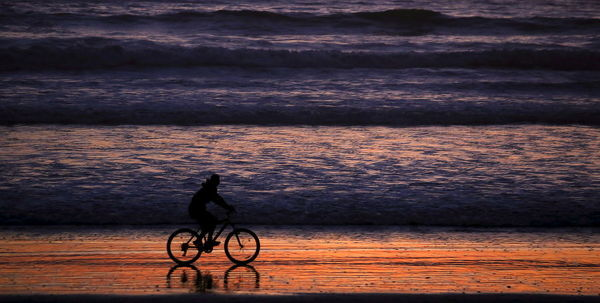 A woman rides her bicycle at sunset on a beach in La Serena, Chile, June 18, 2015. La Serena is home to La Portada stadium, one of the venues where the Copa America Chile 2015 Group B soccer matches are held. REUTERS/Marcos Brindicci - GF