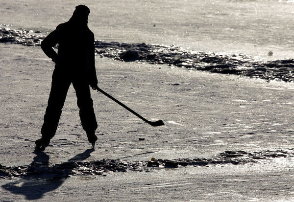 A young boy enjoys playing ice hockey on the frozen part of Vltava river near the centre of Prague January 24, 2006. Europe has been suffering a severe cold wave with temperatures dropping to around -20 degrees Celsius (-4Fahrenheit)