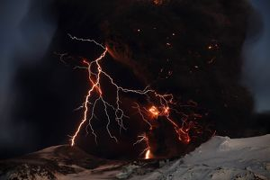 Lightning streaks across the sky as lava flows from a volcano in Eyjafjallajokul